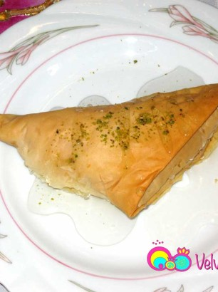Shaabiyat served warm with syrup and ground pistachios.