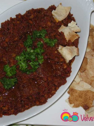 Plate the muhammarah and sprinkle some olive oil and garnish with parsley.