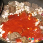 Dilute the tomato sauce with the water and pour into the pot with the meat and beans.
